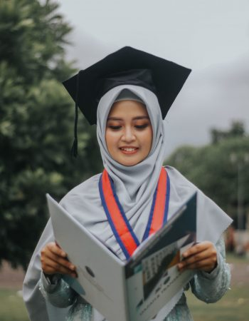 woman-in-white-academic-dress-holding-book-3660654